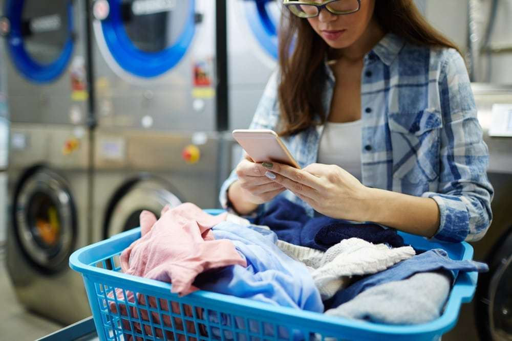 Girl using smartphone while at a laundromat