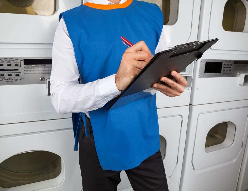 Laundromat manager in blue vest holding clipboard