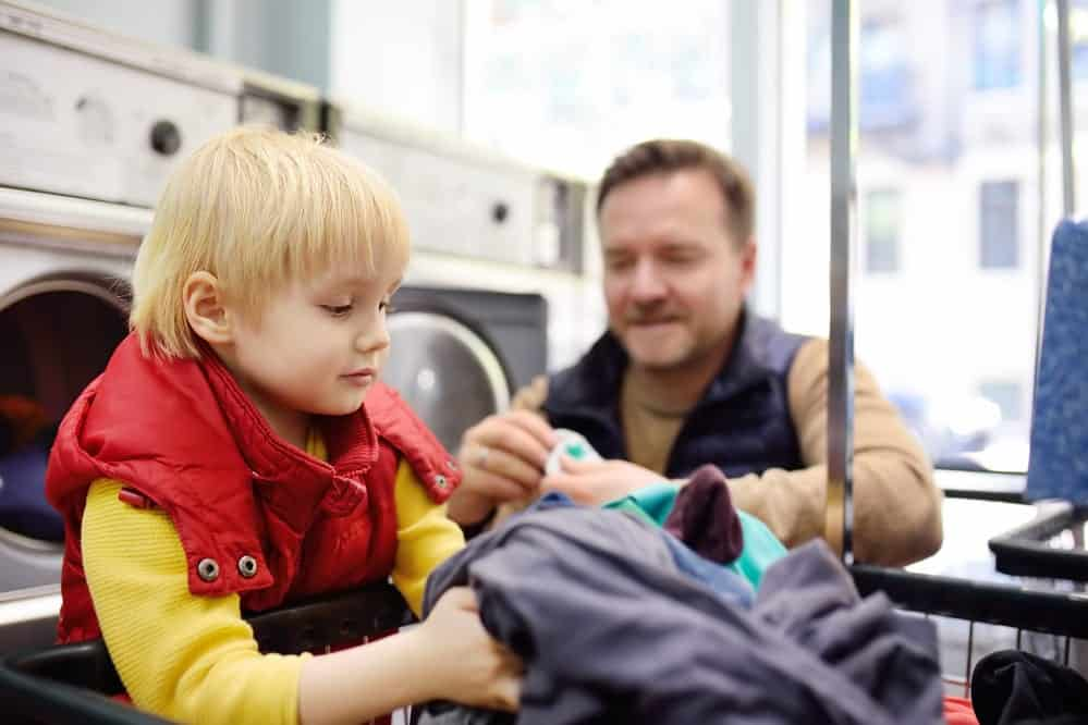 A little boy loads clothes into the washing machine in public laundrette