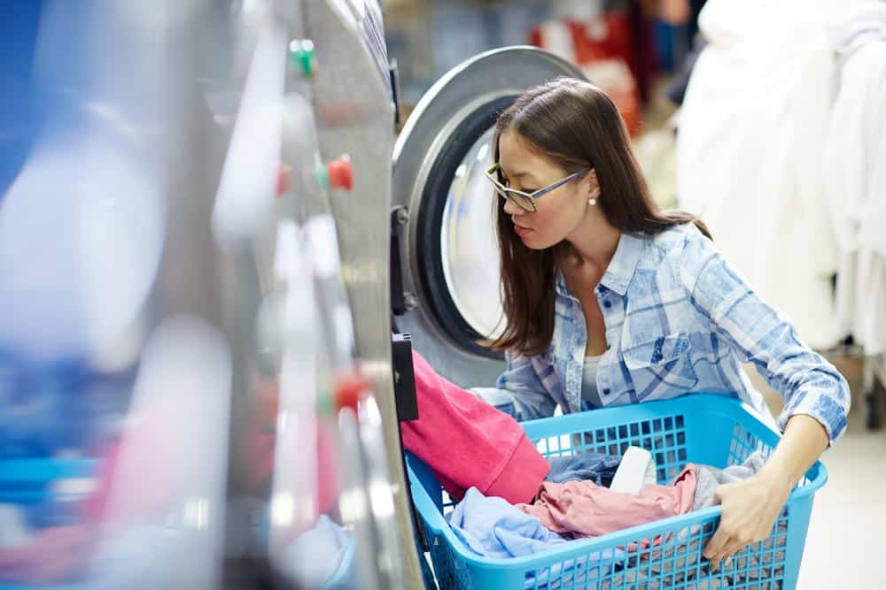 Young woman pulling clothes out of dryer at laundromat