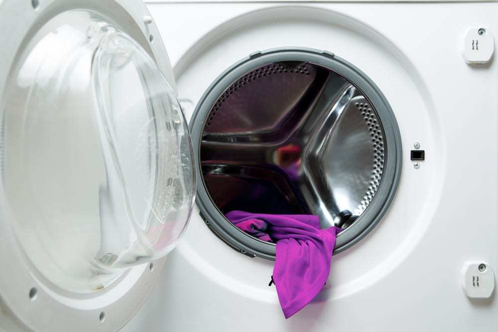 Open washing machine with purple cloth inside