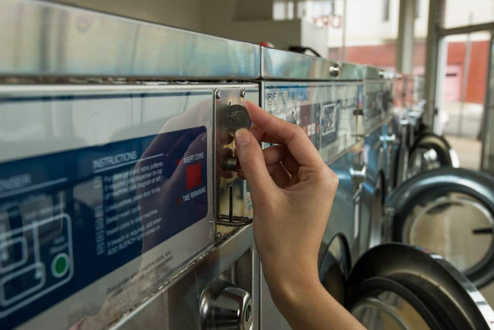 Close-up of hand inserting quarter into laundry machine in laundromat