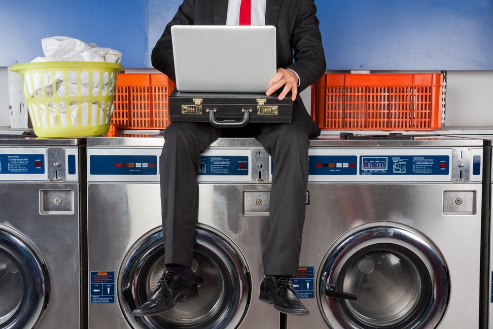 Businessman in suit looking at laptop while sitting on washer at laundromat